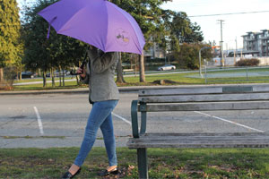 A woman holding a purple umbrella symbolizing shelter against inclement weather